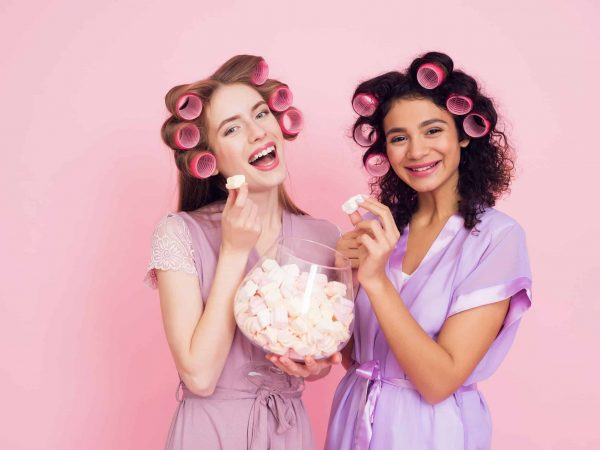 Two girls in robes with hair curlers eating marshmellows. They are celebrating women's day March 8.