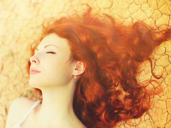 Beautiful young woman portrait with long curly red hair lying on the dried up ground.