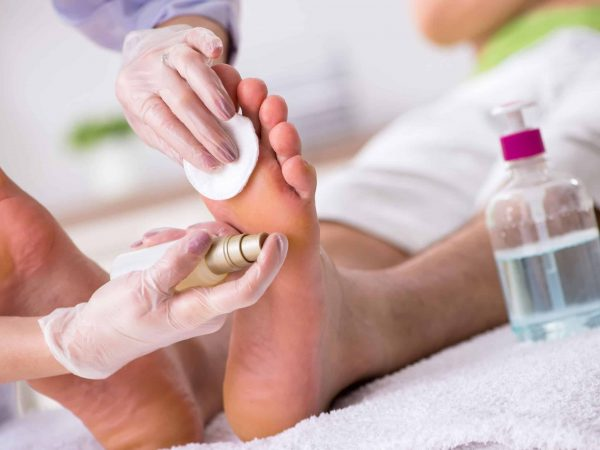 Podiatrist treating feet during procedure