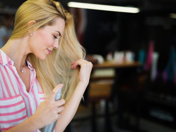 Beauty woman fixes her hair with a hairspray